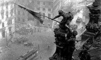 La bandera roja ondeando sobre el Reichstag, el parlamento alemán en Berlín, en mayo de 1945. Ismailov es el que aparece con gorra de plato, aguantando a Kovoliov para que no pierda el equilibrio. Foto: AP
