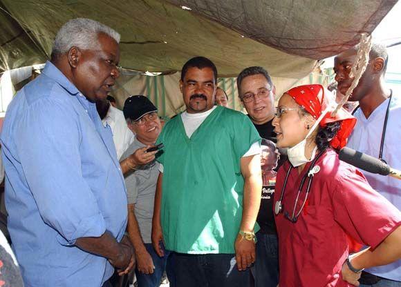 Esteban Lazo (I), miembro del Buró Político del Partido Comunista de Cuba, intercambia con una de las doctoras norteamericanas graduadas en la ELAM en el hospital de campaña de Croix des Bouquets, Haití, durante una visita de trabajo a Haití el 8 de febrero de 2010. AIN Foto: Juvenal Balan Neyra