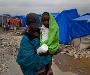 Un hombre alza a un niño en un campamento de sobrevivientes del terremoto haitiano inundado por intensas lluvias en Puerto Príncipe, viernes 19 de marzo de 2010. (AP Foto/Ramon Espinosa)