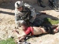 Soldados sonriendo al lado de cadaver afgáno