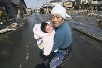 La bebé en brazos de su padre. (Foto AP)