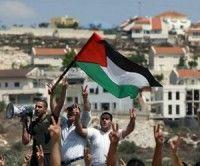 Manifestantes palestinos ondean su bandera durante una protesta por el corte de una carretera por colonos israelíes del asentamiento de Kadumim, en el pueblo de Kfar Kadum en Cisjordania. Foto: AFP