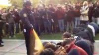 En esta imagen tomada de un video, un agente policial rocía con gas pimienta a un grupo de manifestantes sentados en la Universidad de California en Davis, el viernes 18 de noviembre del 2011. Foto: AP/Thomas K. Fowler
