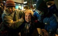 Dorli Rainey, una mujer de 84 años es acompañada por dos Ocupa con la cara cubierta totalmente de aerosol de gas pimienta.