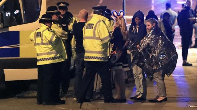Servicios de emergencia y policías hablan con público del concierto a las afueras del Manchester Arena, tras el atentado (Peter Byrne / AP)